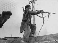 A mujahadeen rebel fires his machine gun as another takes cover in Kabul, Monday, April 27, 1992.