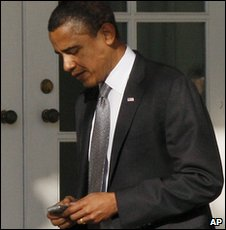 President Barack Obama checks his BlackBerry at the White House