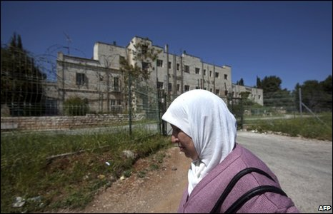 A Palestinian woman passes a site in East Jerusalem designated for new Israeli homes, 24 March