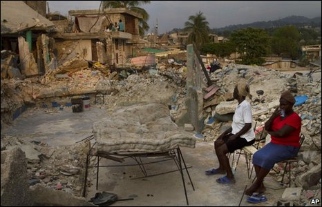 Women sit in the ruins of their home in the Fort Nationale area of Port-au-Prince, 24 March