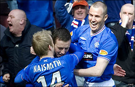 Danny wilson is congratuated by Kenny Miller and Steven Naismith