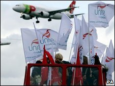 A plane flies over the picket line