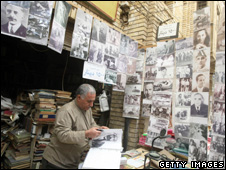 An Iraqi book seller displays historical images of Iraqi political figures for sale at his stall in Baghdad's Shorja market