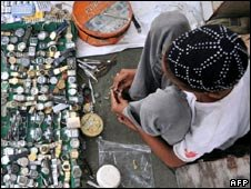 A Pakistani vendor repairs wrist watches