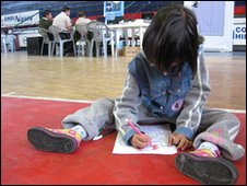 Young child draws on the ground while the registration process takes place