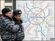 Police stand  near a map of the Moscow Metro, 29 March