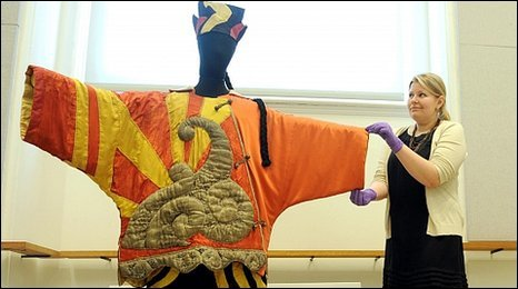 A member of staff adjusts a costume titled Costume for the Chinese Conjuror by Pablo Picasso