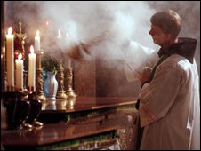 A priest waves incense over an altar inside the Church of the Holy Sepulchre in Jerusalem