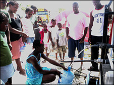 People collect water from a solar-powered pump in Bon Repos