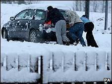 People push a car through the snow near Denny, Central Scotland