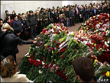 Russians stand near a growing mound of flowers commemorating the victims of the metro blasts inside the Lubyanka metro station  (30 March 2010)