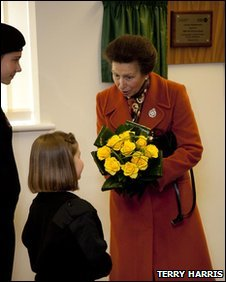Princess Anne holidng flowers and speaking to a small girl