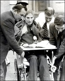 Roger Addison is helped while in a wheelchair