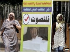 Women walk past election poster in Khartoum