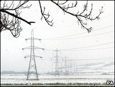 Electricity pylons in snowy field