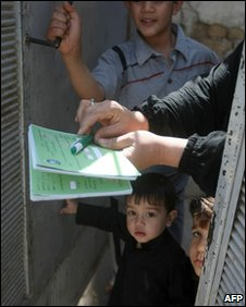 An Iraqi woman hands in her voting paper, 2 April 2010