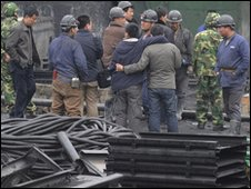 """Miners wait for news of their colleagues at the entrance to a flooded mine shaft at Wangjialing coal mine, in northern China""""s Shanxi province on March 29, 2010"""