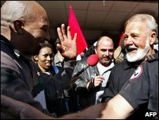 Eugene Terreblanche (R) is greeted by a die-hard supporters as he walks out of jail in June 2004