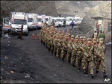 Members of the Chinese paramilitary police march past a row of ambulances parked outside the mine in Shanxi province