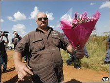 An AWB supporter brings flowers to the gate of Eugene Terreblanche's property near Ventersdrop, west of Johannesburg, South Africa, 4 April 2010