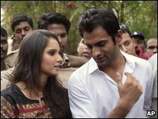 "Indian tennis star Sania Mirza, left and Pakistan""s former cricket captain Shoaib Malik, right, share a moment as they address the media in Hyderabad, India, Monday, April 5, 2010."