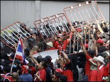Anti-government protesters use barriers to push back riot police in Bangkok, Thailand, 6 April 2010