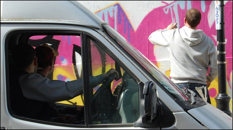 Graffiti artist Scott King is watched by two people in a van, Ipswich