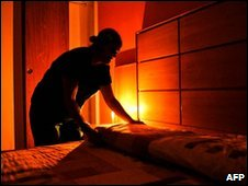 A chambermaid makes a bed in a darkened Caracas hotel room