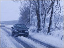 Car travelling through heavy, driving snow along a snow-covered road. Bare trees covered in a layer of snow to the right of the car.