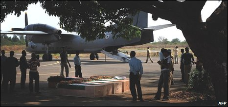 Indian paramilitary officials walk past coffins of slain Indian Central Reserve Police Force (CRPF) servicemen at an airfield in Jagdalpur, around 300kms from Raipur, on April 7, 2010.
