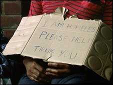 Man holding homeless sign