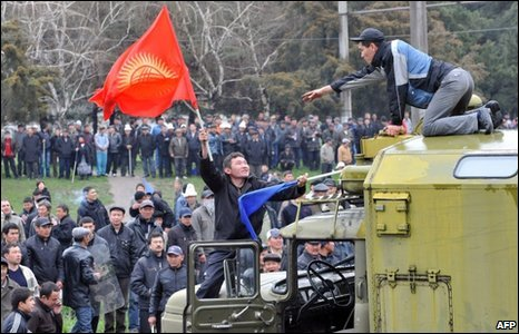 A Kyrgyz opposition supporter hands a national flag to a fellow demonstrator standing on a military vehicle during an anti-government protest in Bishkek, 7 April, 2010