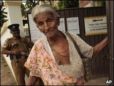 A Sri Lankan police officer stands guard as a woman leaves a polling station