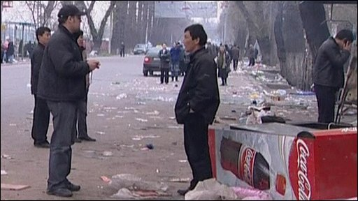 Men standing near piles of debris