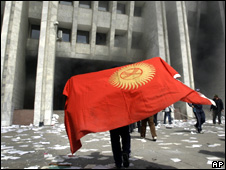 "A man holds a Kyrgyz flag near the ""White House"" in Bishkek"