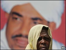 A Sudanese woman stands in front of an electoral picture of Sudanese President Omar al-Bashir in Khartoum