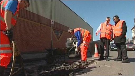 Workmen repairing potholes