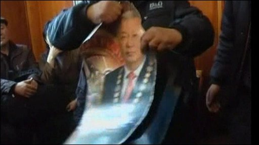 Anti-government protesters destroy a picture of Kyrgyzstan's President Kurmanbek Bakiyev