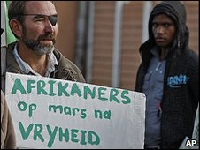 A supporter of slain white supremacist leader Eugene Terreblanche holds a placard reading, Afrikaners on the march to freedom, outside the court in Ventersdorp, South Africa, Tuesday, April 6, 2010