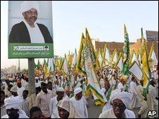 Sudanese pass under billboard of President Omar al-Bashir
