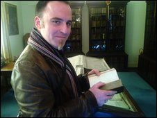 Benjamin Till holds Pepys' diary, with his bookcases behind.