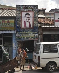 A Colombo municipal worker sweeps as a boy looks on under the poster of Sri Lankan President Mahinda Rajapaksa, in Colombo, Sri Lanka, Friday, April 9, 2010.