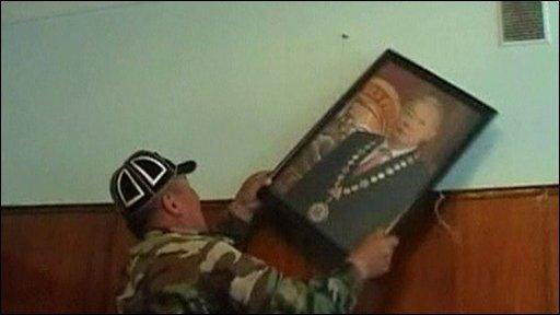 Opposition protester removesa picture President Bakiyev
