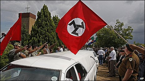 Supporters of slain white supremacist leader Eugene Terreblanche, salute the coffin as it leaves the church in Ventersdorp, South Africa, Friday, April 9, 2010.