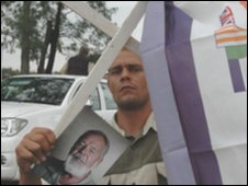 A supporter of Mr Terreblanche holds up his picture beneath a cross