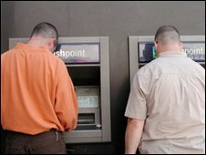 Two men using cash machines