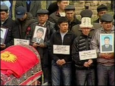 Mourners hold pictures and the names of the 15 victims being buried at the meorial site in Kyrgyzstan