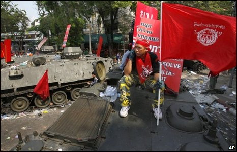A red-shirt protester sits atop an armourned personnel carrier in Bangkok on 11 April