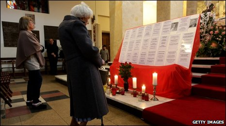 Women pause at a makeshift shrine at St. Stanislaw Kostka church, 11 April 2010 in Warsaw, Poland