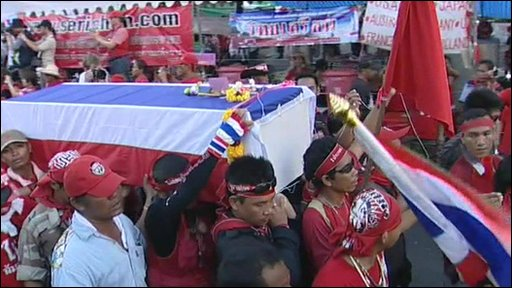 A coffin draped in the Thai flag is carried towards Democracy Monument